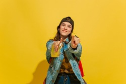 Smiles, pointing on. Portrait of a cheerful young caucasian tourist girl with bag in jeans clothes isolated on yellow studio background. Preparing for traveling. Resort, human emotions, vacation.