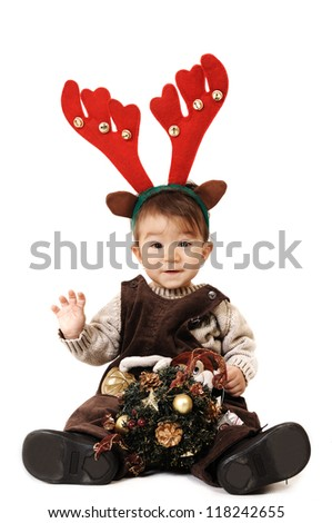 Smiley baby dressed as a reindeer is waving his hand