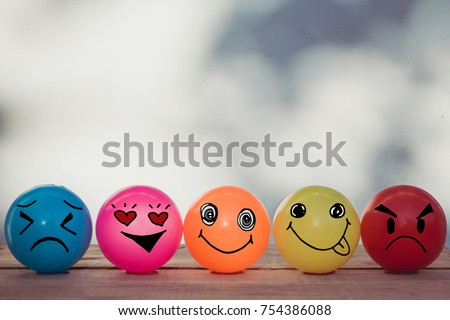 Smiley balls and Emotion balls on wooden table with bokeh wall background and copy space #754386088