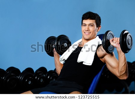 Smiley bodybuilder exercises with weights in fitness gym against a set of dumbbells