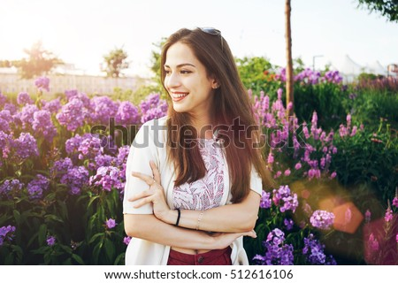 Smiley brunette girl is looking aside while standing outdoors on the flowers and bushes background at the city park. Model look woman is smiling while walking at the garden on sunset.
