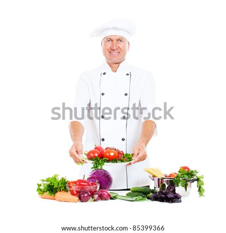 smiley chef holding plate with fresh vegetables. isolated on white background