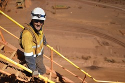 Smiley construction miner wearing safety helmet glove dressing work uniform having a break walking down stairs maintenance safety fall prevention using holding handrails three points of contact