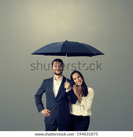 smiley couple under umbrella over dark background