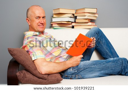 smiley elderly man reading interesting book at home