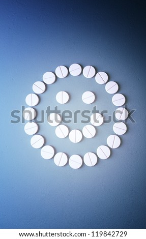 Smiley face from pills on blue background