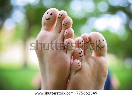 smiley faces on a pair of feet on all ten toes in a park on a hot summer day  #775662349