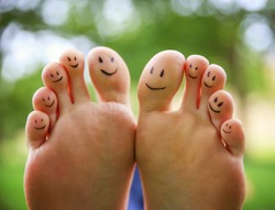 smiley faces on a pair of feet on all ten toes (VERY SHALLOW DOF - big toe on the right) in a park setting