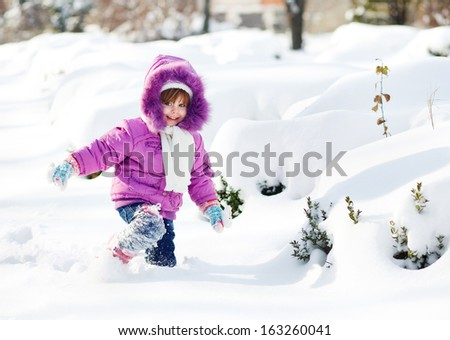 Smiley girl in the snow in purple clothes