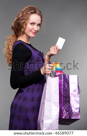 smiley girl with credit card and paper bags against grey background