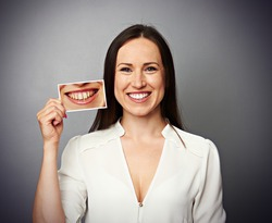 smiley healthy woman holding picture with dirty yellow teeth