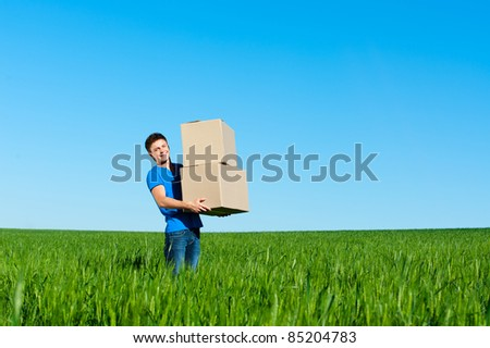 smiley man in blue t-shirt carrying boxes