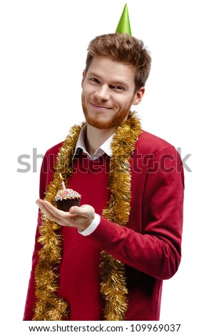 Smiley man with tinsel and fool's cap holds small cake, isolated on white - stock photo
