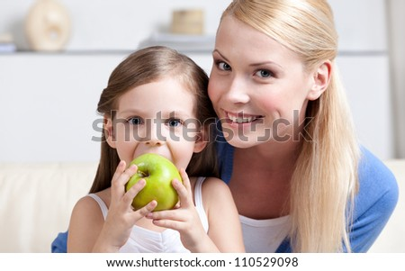 Smiley mom with her eating green apple daughter #110529098