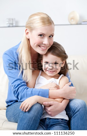 Smiley mother hugs her daughter on the sofa