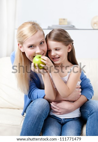 Smiley mother with her eating green apple daughter
