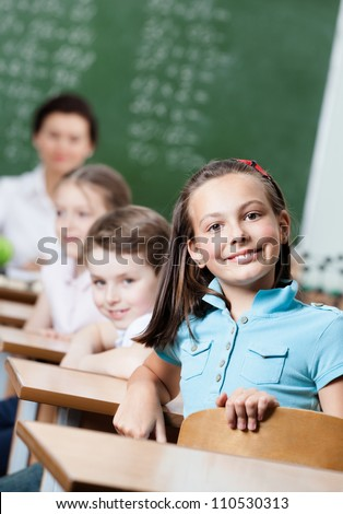 Smiley schoolgirl sits at the desk at math lesson
