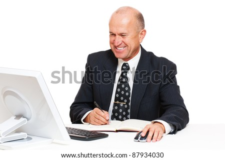 smiley senior businessman sitting in workplace and writing in datebook