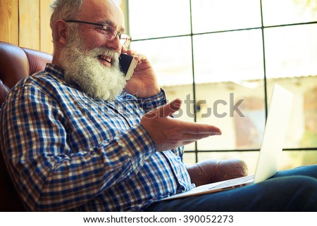 smiley senior man sitting on the couch with laptop and talking on the phone at home #390052273