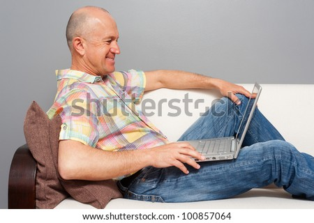 smiley senior man with notebook lying on the sofa at home