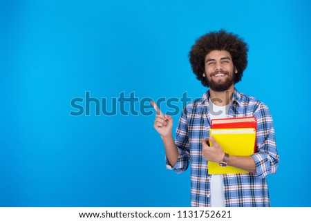 Smiley student holding books pointing up with one finger got a good idea isolated on white background.