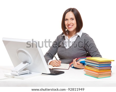 smiley student  with books sitting on her workplace. isolated on white background