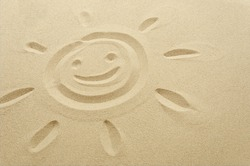 smiley sun face drawn in sand, empty space on the right, sandy beach, summer vacation, beach holiday, happy smiling face of sun