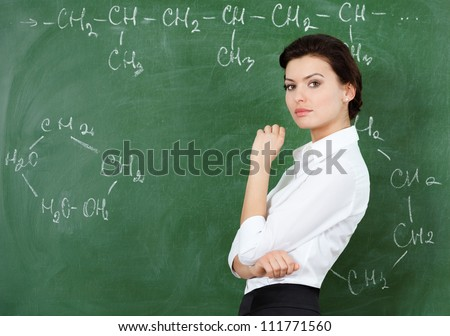 Smiley teacher at the chalkboard writes a chemical formula