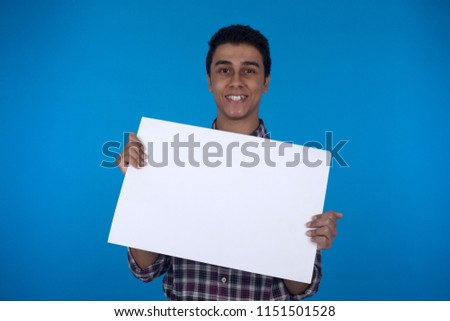 Smiley teenager holds one paper in horizontal pose on a blue background.