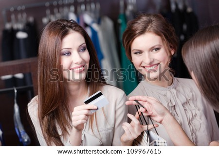 Smiley women pay with credit card for purchases