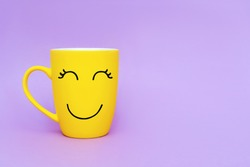 Smiley yellow coffee cup on purple background. Happy friday word concept.