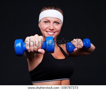 smiley young female doing exercises with dumbbells. focus on fist