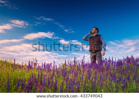 Smiley young man, standing on a green grass field with wild flowers (lupine), talking by phone against blue sky. #433749043