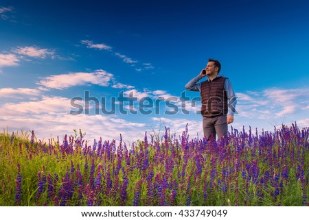 Smiley young man, standing on a green grass field with wild flowers (lupine), talking by phone against blue sky. #433749049