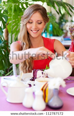 smiley young woman sitting in cafe and pouring cup of tea