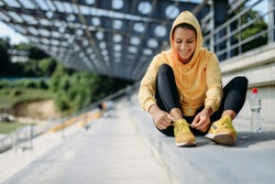 Smiling active female in yellow sweater with hood on head adjusting her laces on sneakers before workout outside. Healthy young woman enjoying regular training on fresh air.