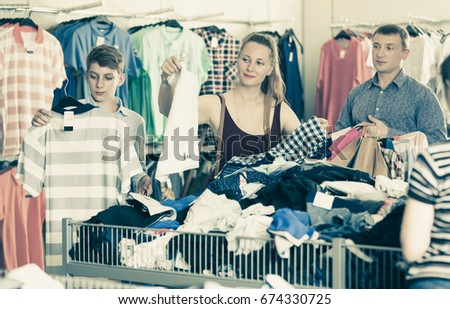 e0e697e947 Young smiling man holding clothes in the clothing store Images and ...