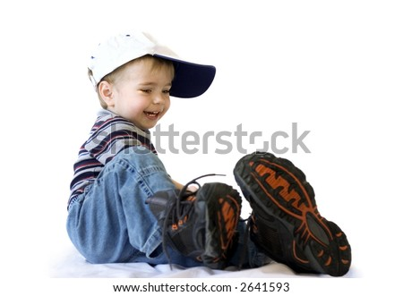 Smiling adorable baby in blue jeans and big shoes