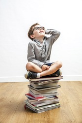smiling adorable child with eyeglasses seated on top of a pile of books looking up for concept of school education, culture and open-mindedness, wooden floor