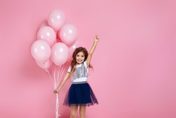 Smiling adorable little child girl posing with pastel pink air balloons isolated over pink background. Beautiful happy kid on a birthday party. copy space
