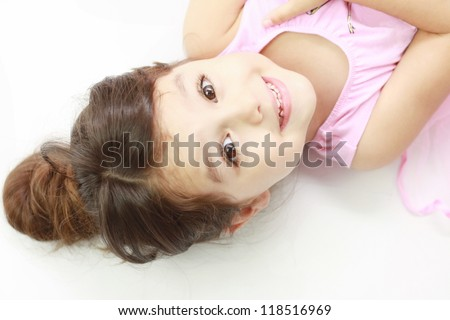 Smiling adorable little girl lying down, looking straight into the camera with focus on her face