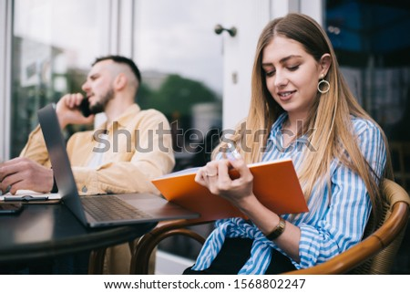 Smiling adult female in casual outfit writing on notebook while sitting at table with blurred adult male having phone call working remotely in terrace of cafe