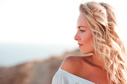 Smiling adult girl with curly blonde hair looking away over sea background. Side view. Summer portrait. 20s.
