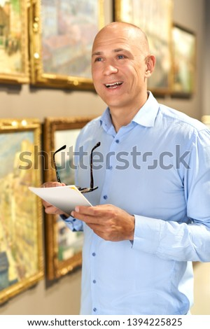 Smiling adult man considers exhibits in museum