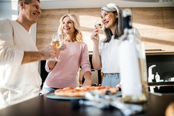 Smiling adult three friends drinking wine and eating pizza stock photo. Friendship and holidays concept