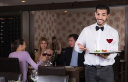 smiling adult waiter with serving tray meeting restaurant guests