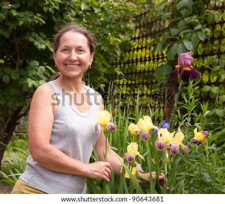 Smiling adult woman with flowers of   iris in her garden