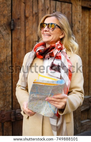 Smiling adult woman 60-65 years old with sunglasses. Traveled by Europe with map in hands on background old wooden wall.