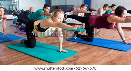 Smiling adults having yoga class in sport club