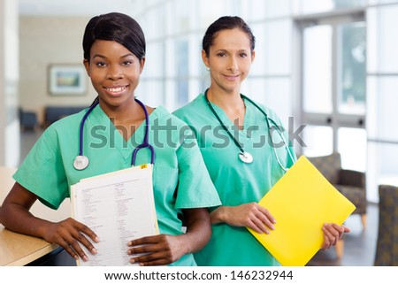 Smiling African American and caucasian nurse at hospital work station lit brightly with carts and wearing stethoscopes.